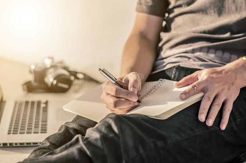 人在笔记本写笔并且研究膝上型计算机,一个人放松workin 库存图片