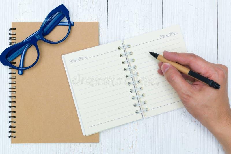 人在笔记本纸空白页的手文字与笔,玻璃的 免版税库存图片