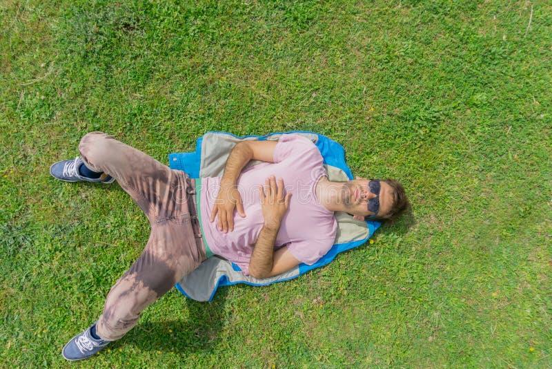 人在绿色草坪说谎 与拷贝空间的顶面和鸟瞰图 免版税库存图片