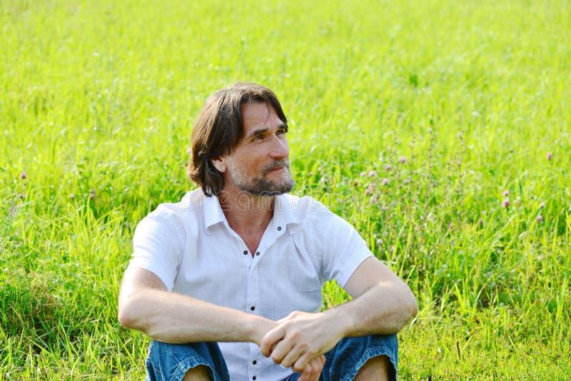 人在草坐在夏天 免版税库存图片