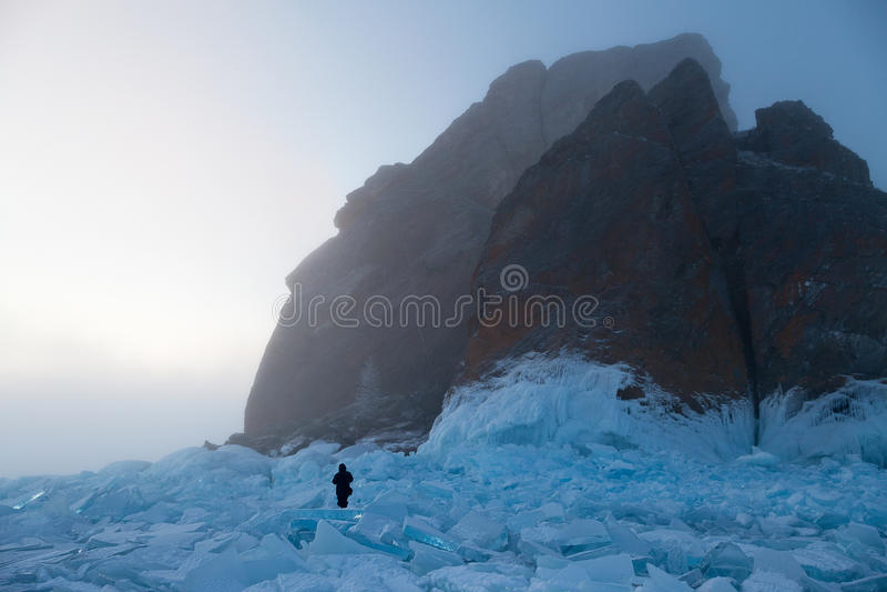 人在蓝色冰中走在雾的计算的岩石附近 免版税库存图片