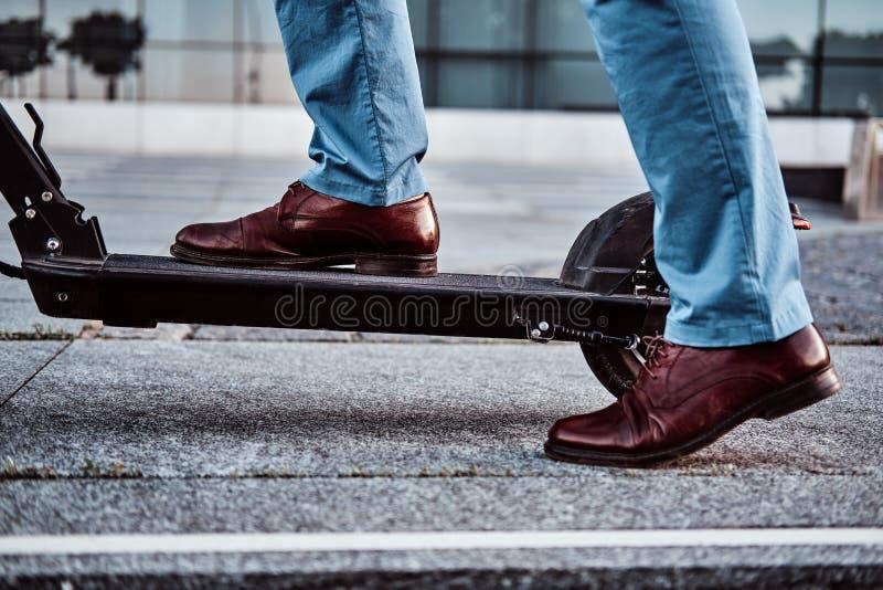 人在街道乘坐他新的滑行车 免版税库存照片