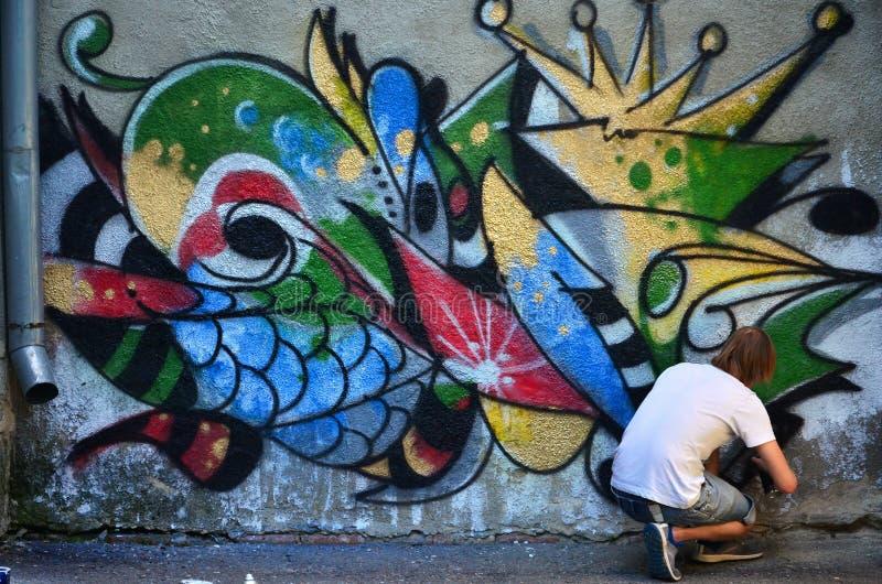 人在街道画墙壁上画与各种各样的颜色湿剂油漆的一张图画  免版税库存图片