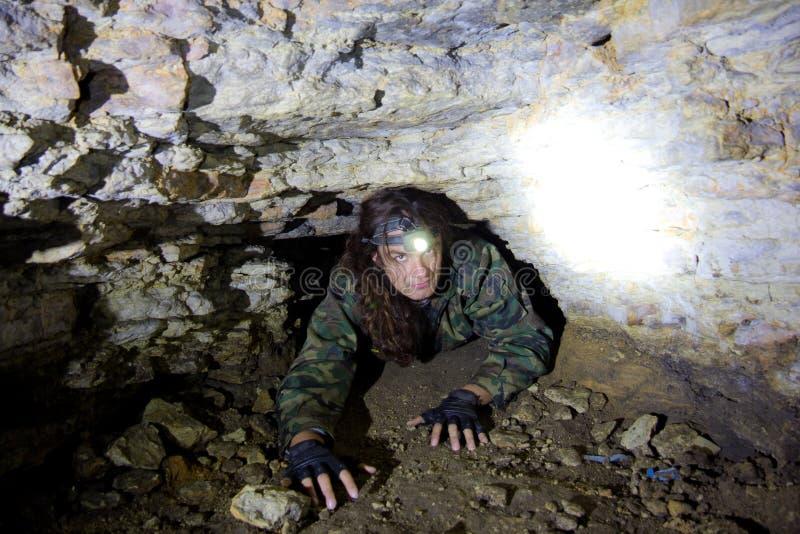 人在被放弃的地下石灰石矿探索狭窄的洞穴段落 图库摄影