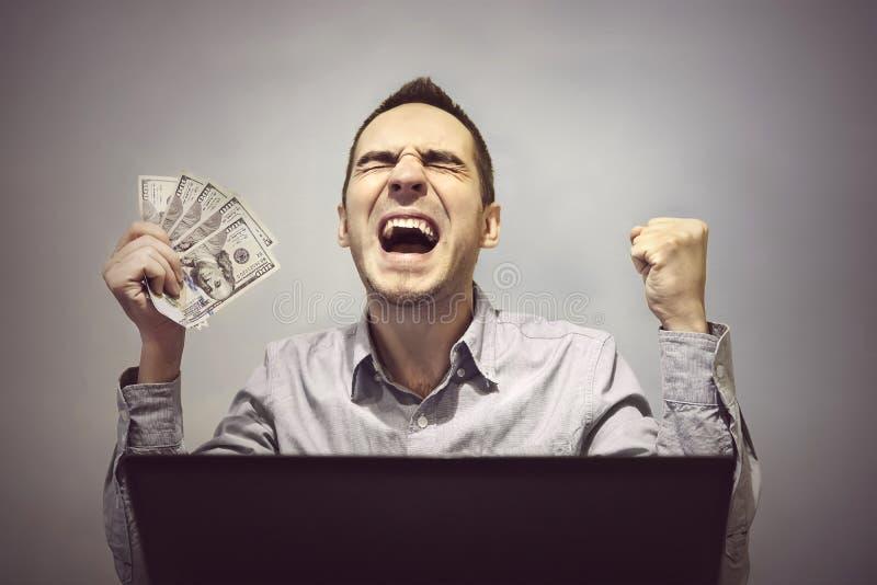 人在计算机前面是愉快拿着500美元 免版税库存照片