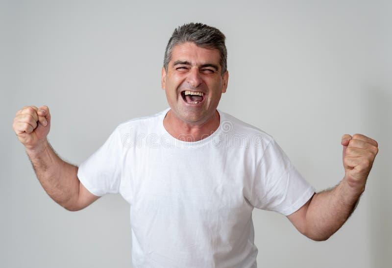 人在达到高兴他的目标,喝酒抽奖或有巨大成功在面孔表示人的情感惊奇和 库存图片