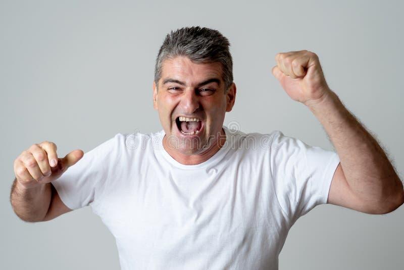 人在达到高兴他的目标,喝酒抽奖或有巨大成功在面孔表示人的情感惊奇和 免版税库存图片
