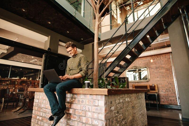 年轻人在运作办公室的自助食堂坐膝上型计算机 免版税库存图片