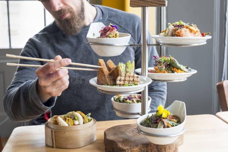 人在餐馆采取从有排列的板材服务器的豆腐 库存图片