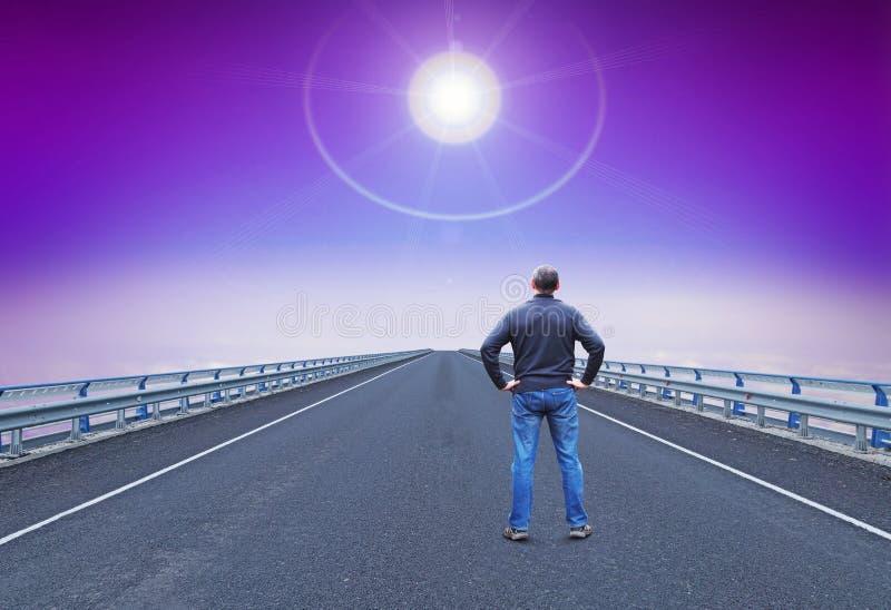 人在高速公路在天际的引导的星站立并且看 免版税库存照片