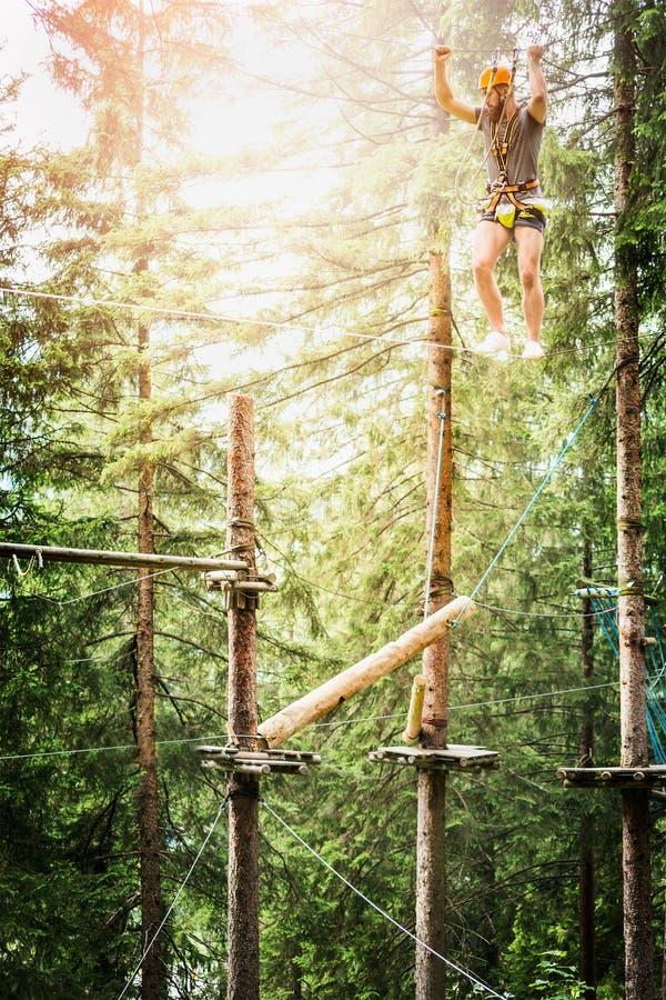 年轻人在绳索上升在自然bakgrund的上升的森林里 免版税库存照片