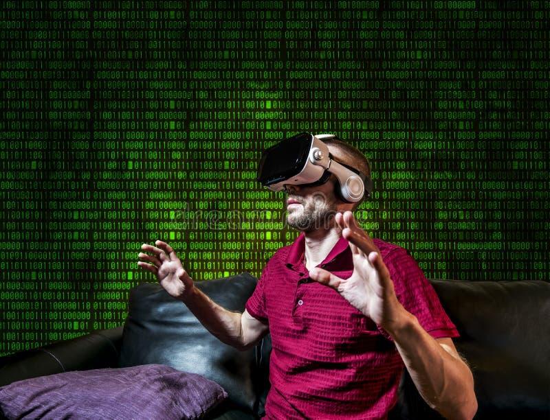 人在玻璃虚拟现实中在背景矩阵使用 库存照片