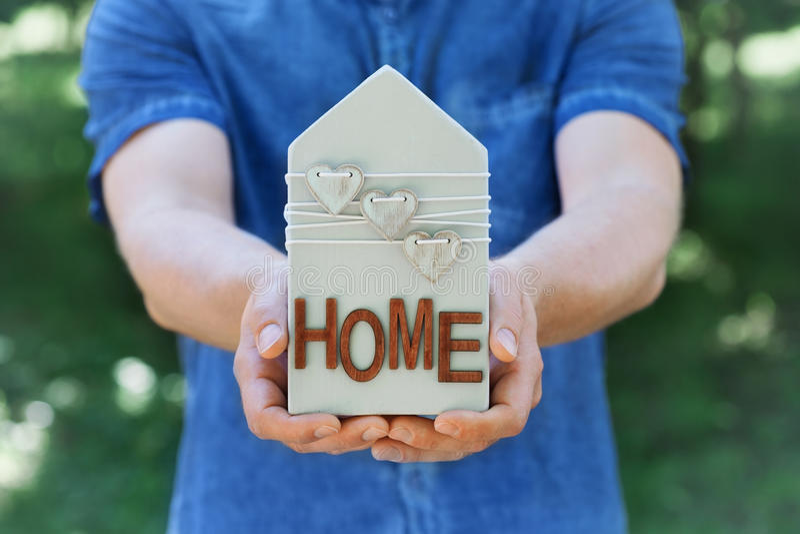 人在他的在绿色自然背景的手木房子装饰的心脏举行 房地产、保险,销售或者买一个新的家 库存图片