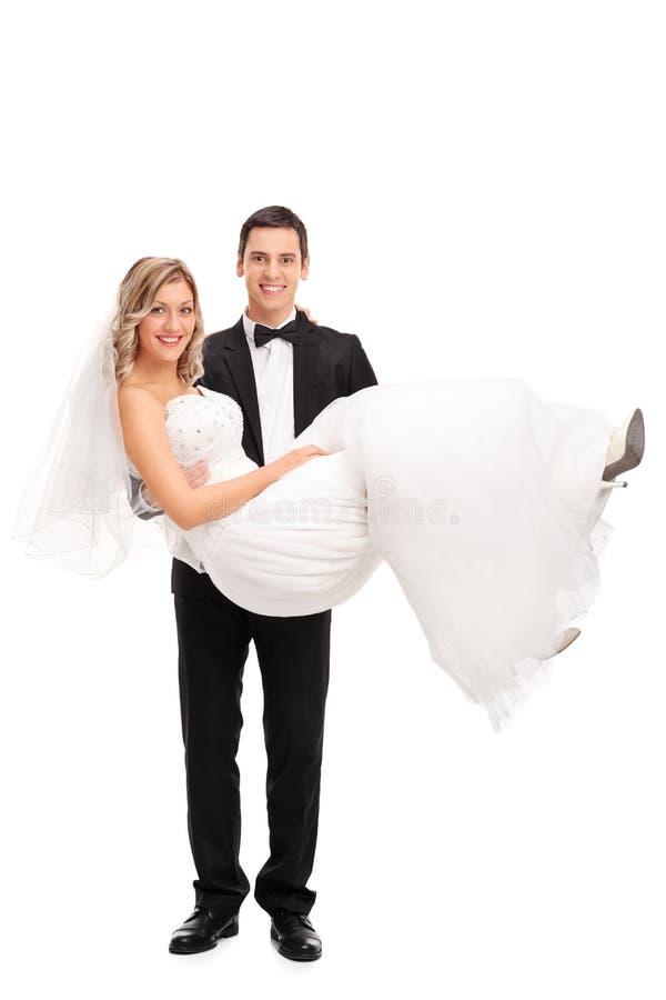 年轻人在他的手上修饰运载一个新娘 免版税库存照片