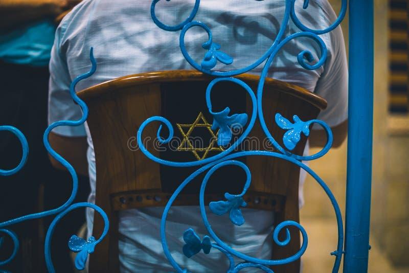 人坐与大卫星标志通过被看见的蓝色篱芭的一把犹太教堂椅子 免版税库存照片