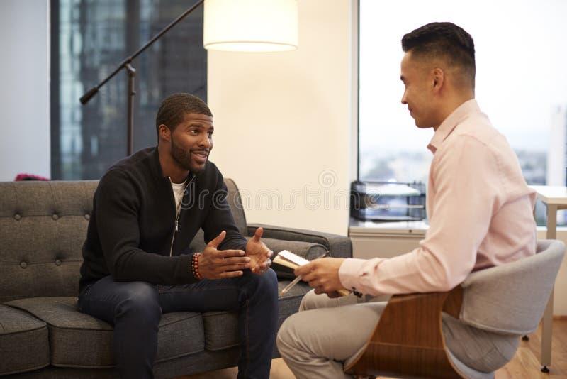 人坐与男性顾问的长沙发会谈在办公室 图库摄影