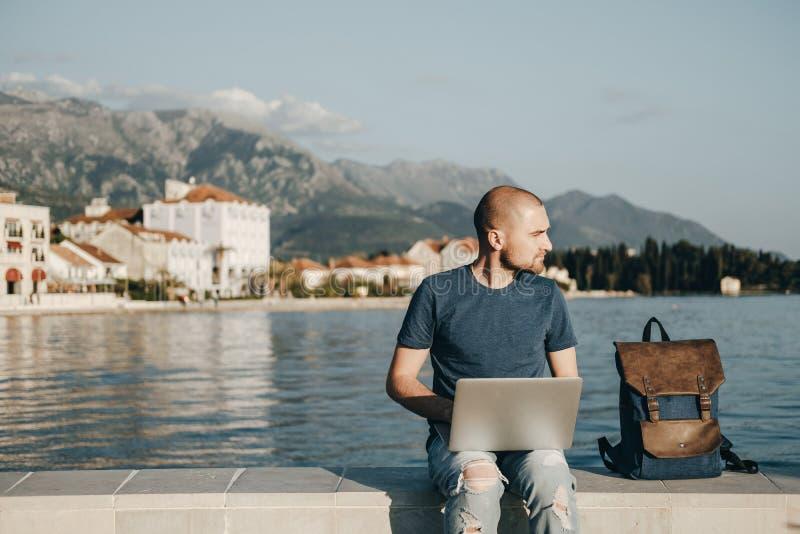 年轻人坐和与便携式计算机一起使用在海附近 免版税库存图片