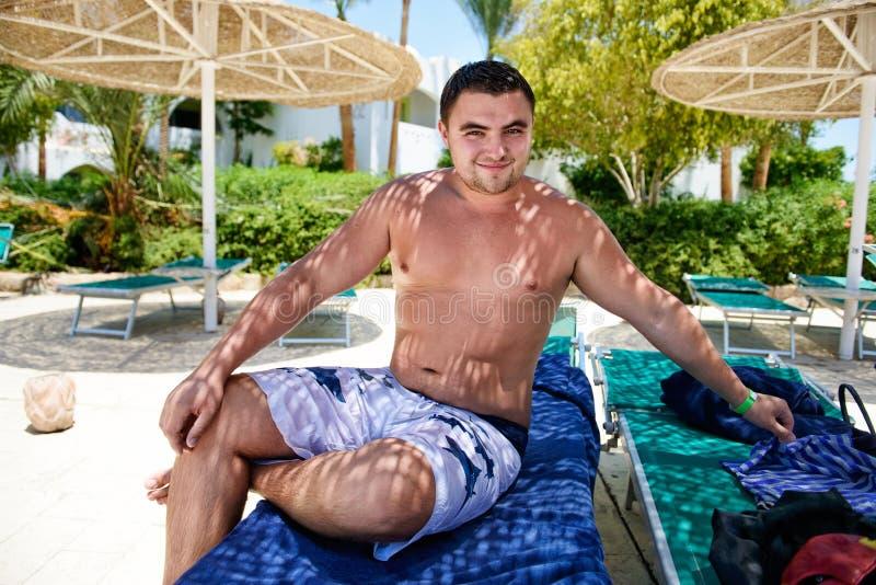年轻人坐在海滩sunbed的 免版税图库摄影