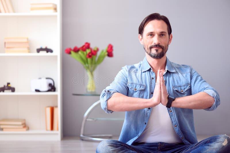 人坐在瑜伽姿势的地板 图库摄影
