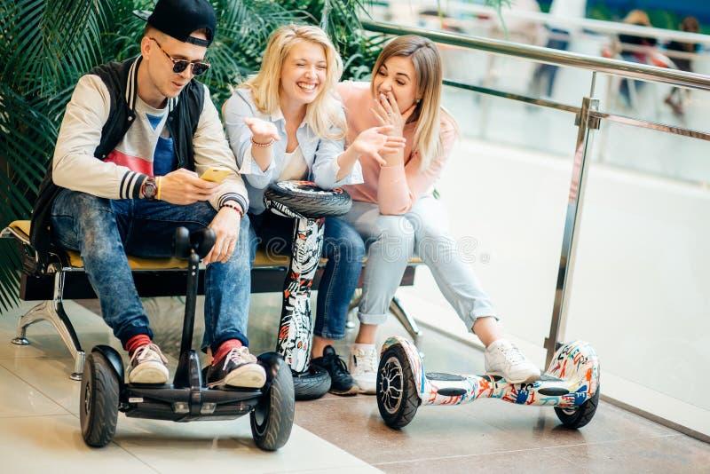 人坐在长凳和使用电话的电滑行车hoverboard的 库存图片