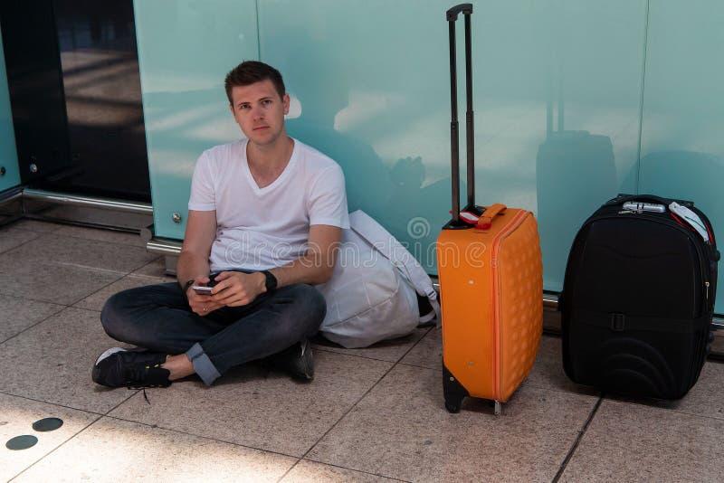人坐地板在机场 白色T恤的浅黑肤色的男人 免版税图库摄影