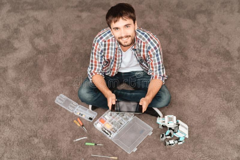 人坐地板 在它旁边是机器人机器人的犀牛、零件和工具 免版税图库摄影