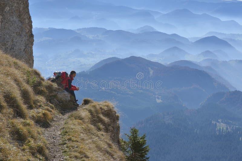 人坐峰顶岩石和观看入五颜六色的薄雾和雾在森林谷 库存照片