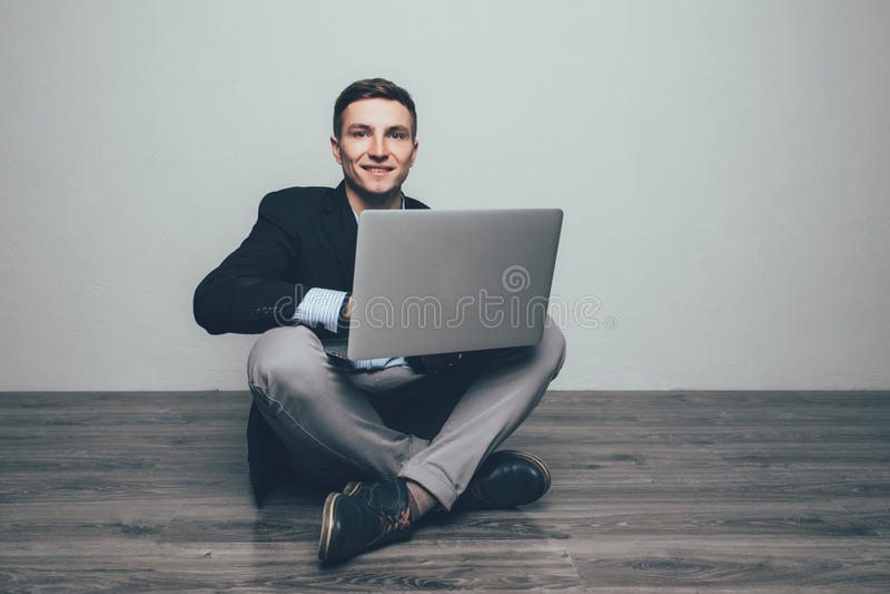 年轻人坐木地板,使用膝上型计算机 黑色通信概念收货人电话 免版税库存照片