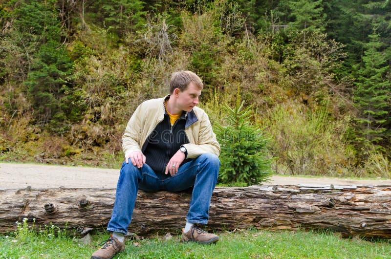 年轻人坐树干 免版税库存图片