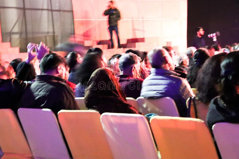 人坐活的椅子和观看的阶段的表现 免版税库存照片