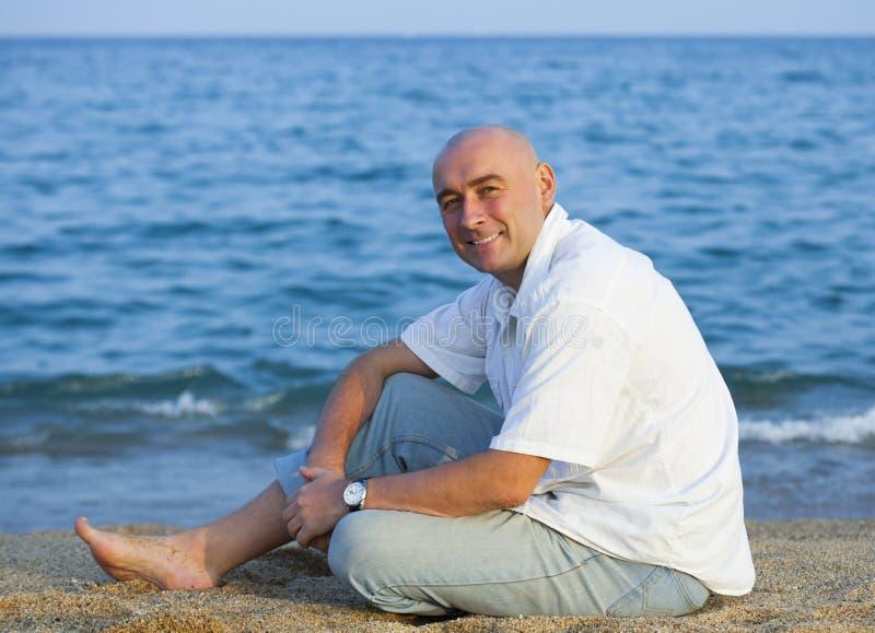 人坐海滩在海附近 免版税库存图片
