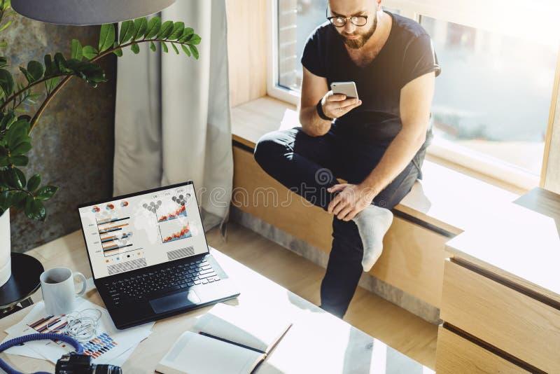 人坐窗台的行家在家读短信,送电子邮件、usig他的电话和快速的互联网连接 库存照片