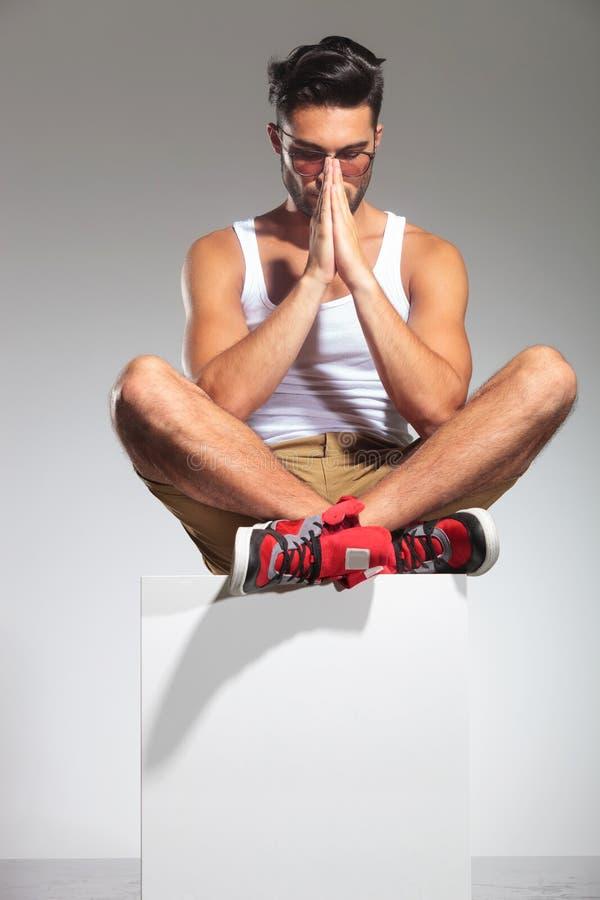 人坐立方体在演播室祈祷 库存照片