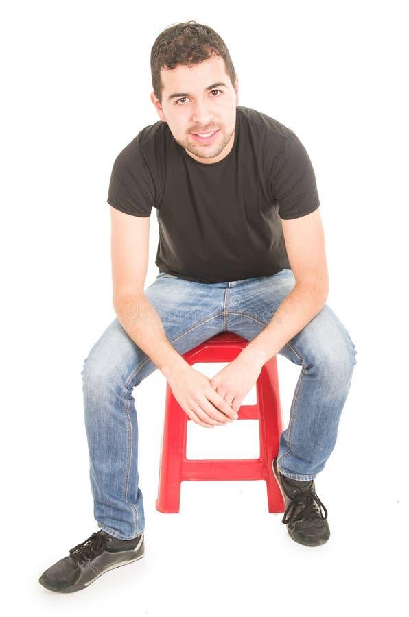 年轻人坐红色凳子 免版税库存照片