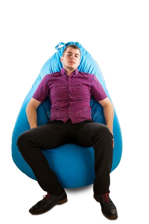 年轻人坐蓝色装豆子小布袋 免版税库存图片