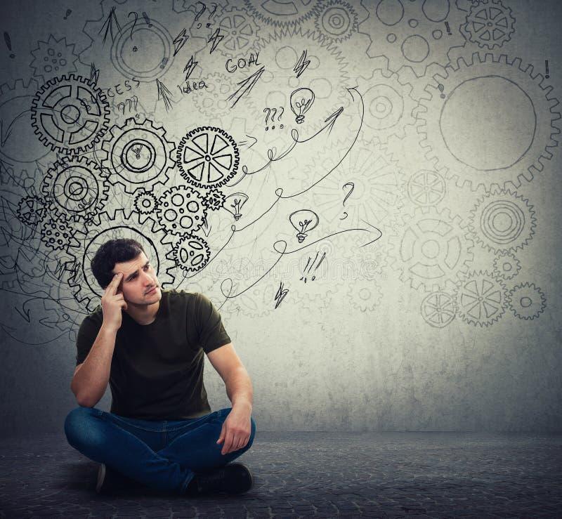 人坐认为的地板,发现一种解答解决问题 另外想象力,供选择的想法 齿轮脑子 库存图片