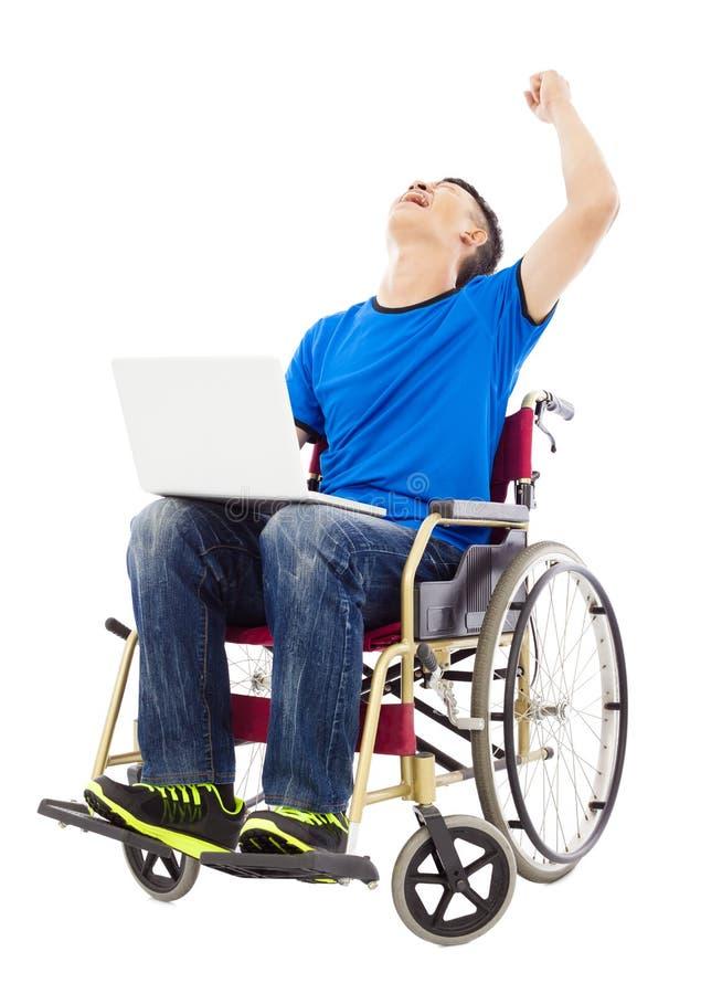 年轻人坐轮椅和激发举胳膊 免版税库存图片