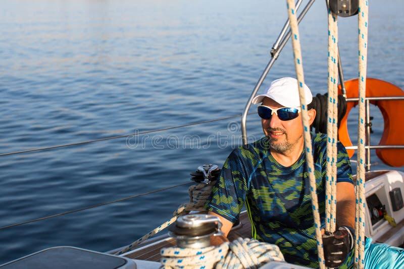 人坐他的航行游艇 体育运动 库存图片