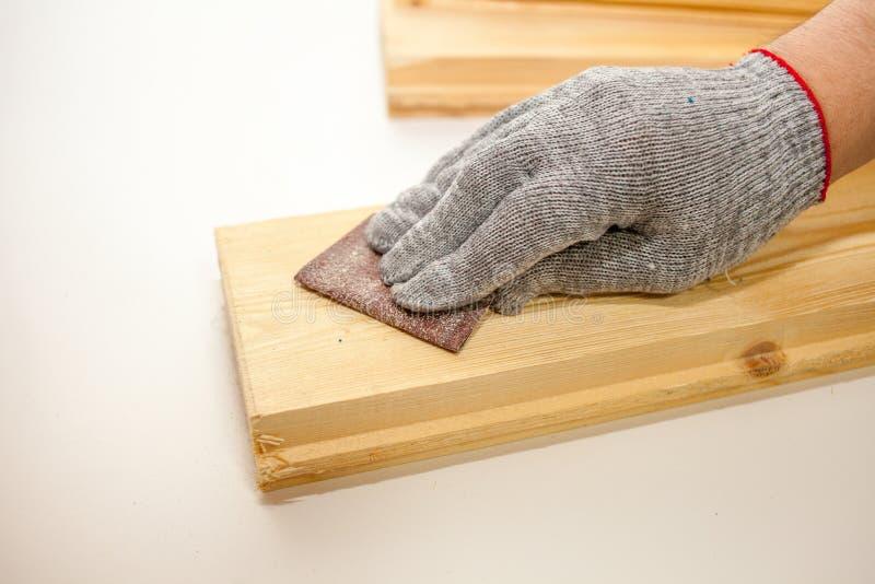 人处理有沙纸的委员会 擦亮的杉木板 图库摄影