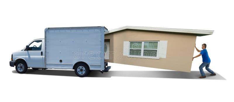 人奋斗填入的家庭房子到移动的卡车搬运车里在天移动 免版税库存照片