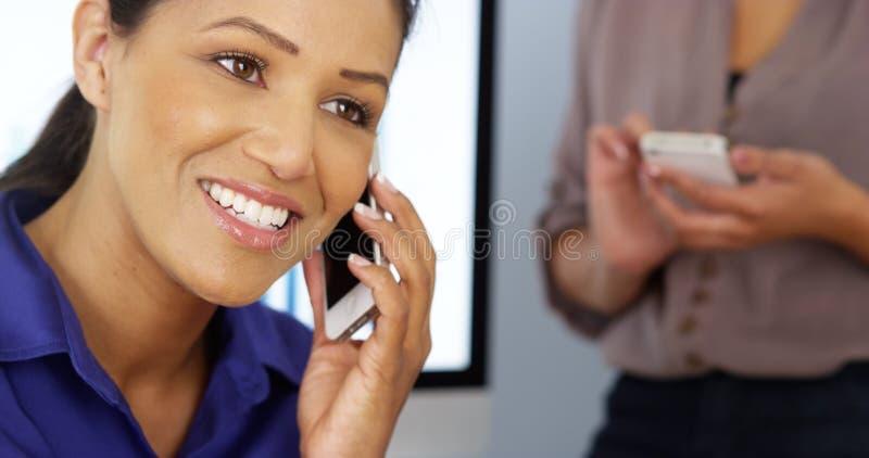 黑人女商人谈话在有工友的电话在背景中 库存图片