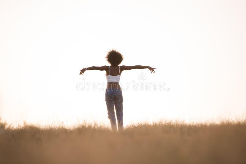 年轻黑人女孩在草甸跳舞户外 库存照片