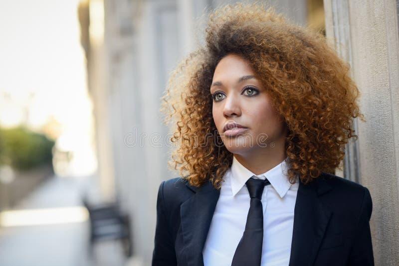黑人女实业家佩带的衣服和领带在都市背景中 库存图片