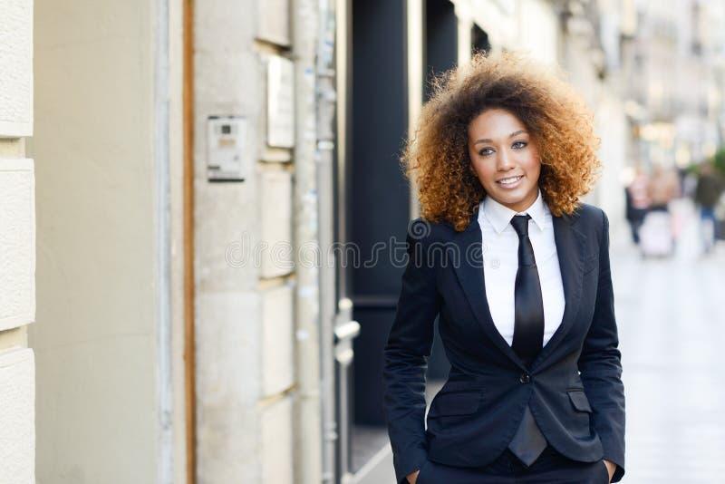 黑人女实业家佩带的衣服和领带在都市背景中 库存照片