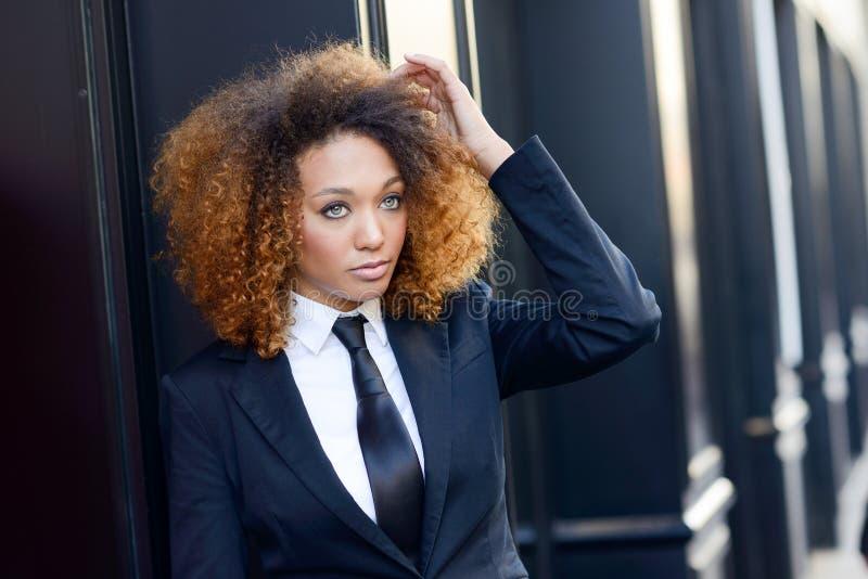 黑人女实业家佩带的衣服和领带在都市背景中 免版税库存照片