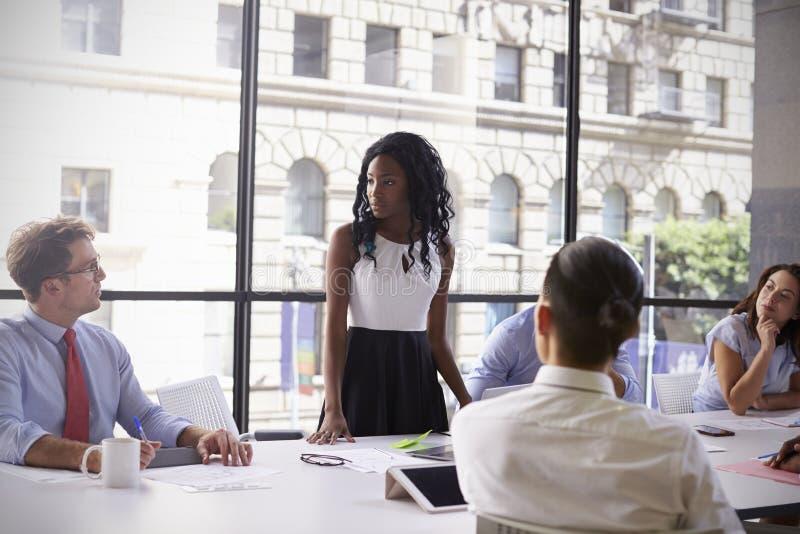 年轻黑人女实业家站立与同事在会议上 免版税图库摄影