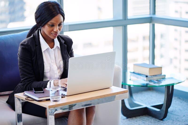 黑人女实业家繁忙工作,当看她的屏幕时 库存照片