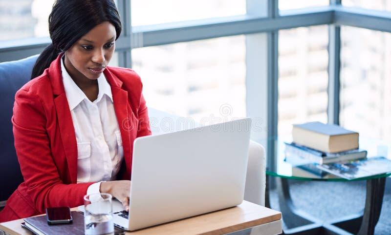 黑人女实业家繁忙工作,当看她的屏幕时 库存图片