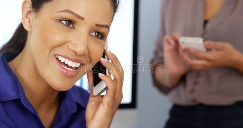 黑人女实业家谈话在有工友的电话在背景中 免版税图库摄影