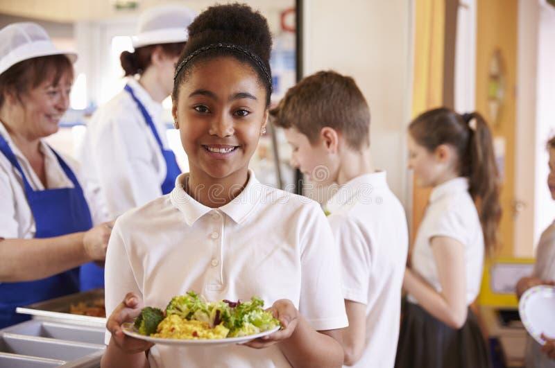 黑人女小学生在学校食堂拿着食物板材  免版税库存照片